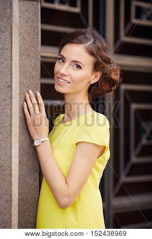 Outdoor Portrait Of Young Beautiful Woman Fashion Model In Yellow Dress On Granite Walls