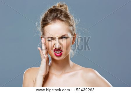 Beautiful blonde nude girl with bright makeup have headache over grey background. Copy space.