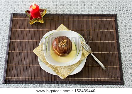 sweet desert with baked apple and candel