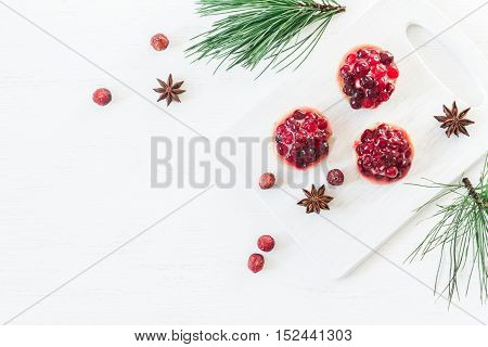 Christmas composition. Christmas dessert of cranberries anise star. pine branches. Flat lay top view