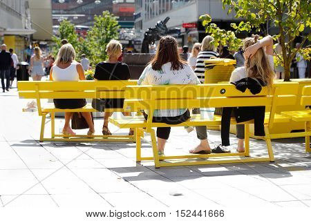 Stockholm, Sweden - August 4, 2015: Summer time at the street Sergel Arkaden in the city center off Stockholm with people sitting on yellow bench in the warm sun light.