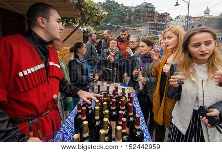TBILISI, GEORGIA - OCT 16, 2016: Women tasting wine with bartender in national georgian costume at festival Tbilisoba on October 16, 2016. Tbilisoba is traditional festival in capital of Georgia from 1979