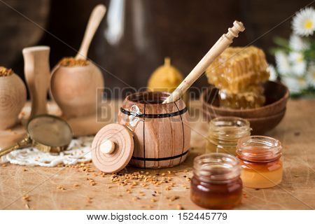 Honey Background. Natural Honey Comb, Glass Jarand Wooden Bowls. On Wooden Rustic Table. Soft Focus