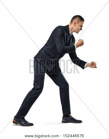 Young businessman posing like he is pulling a rope over his shoulder isolated on a white background. Making efforts. Working hard. Dragging and overcoming something.