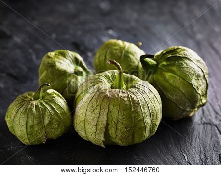 pile of fresh tomatillos in rustic setting
