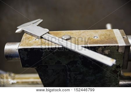 Metal gauge closeup on a metal surface. Caliper on lathe grinder machine.