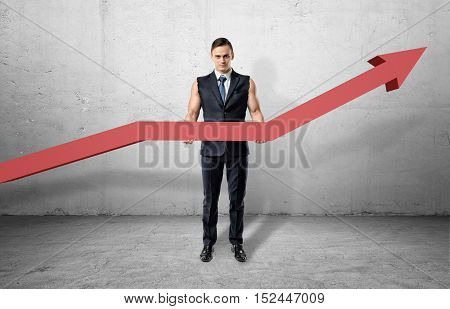 Businessman having muscular arms and holding a big red line graph with an upturned arrow on a grey background. Profit growth indicator. Rate of income increase. Make your business strong.