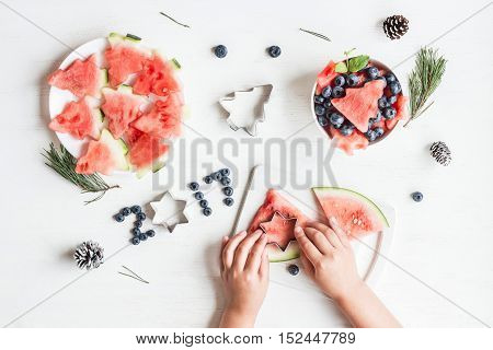 Christmas salad of watermelon and blueberries for kids. Children's hands cooking christmas fruit salad on white table. Top view flat lay