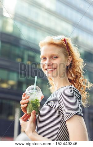 Smiling ginger girl with cocktail in hand on building background, photo toned