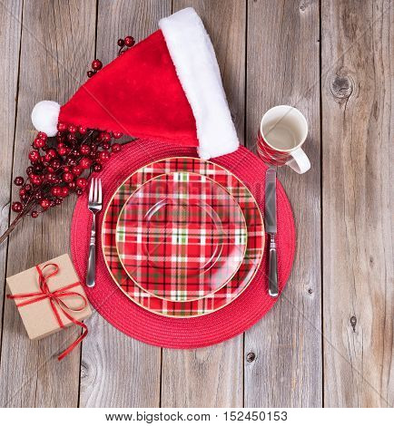 Overhead view of a festive Christmas dinner setting with red berry decorations Santa cap and present on top of rustic wood