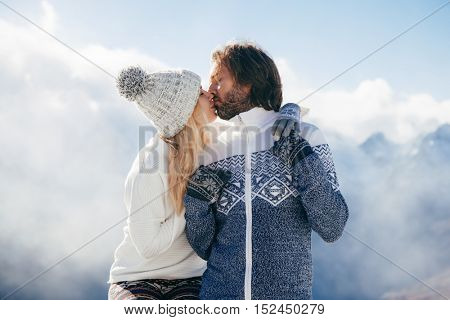 Loving couple kissing in snow outdoor. Winter holidays in mountains. Man and woman wearing knitted clothing resting on weekends.