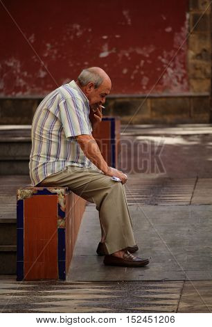 JEREZ DE LA FRONTERA/SPAIN - 6 OCTOBER 2016: Senior man sitting and smoking a cigarette in Jerez de la Frontera old town, Andalusia