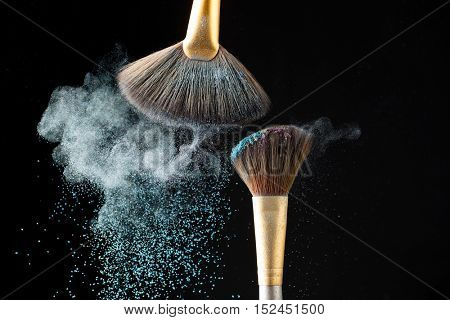 Thick professional brush and loose powder particles scattered around