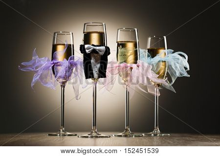 Decorated glasses of champagne in gentleman costume and female tulle