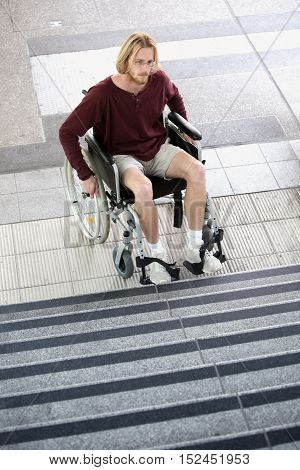 young man sitting in wheel chair in front of stairs and looking sad