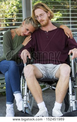 woman hugging young man in wheelchair and looking sad