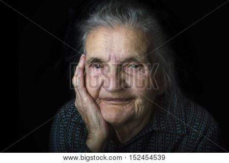 Portrait of a sad nostalgic elderly woman. Evoking the past and worrying about the future. Selective focus.