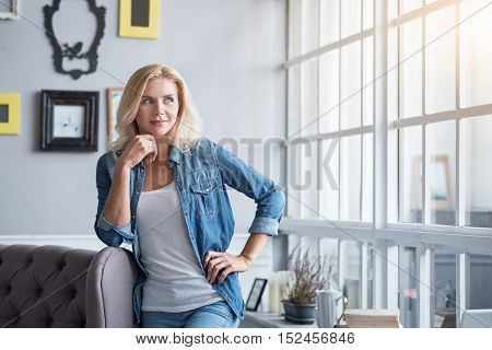 Enjoying sunlight. Pretty blond haired woman standing at grey vintage couch and musingly looking aside.