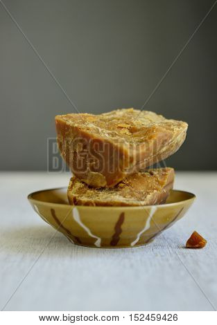 A big piece of brocken Gur block placed in a bowl. Organic 'Gur'- a natural sweetner made with sugarcane molasses is healthy option to the refined sugar.