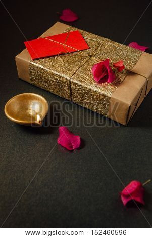 A beautiful gift pack wrapped in a golden paper, tied with golden thread. An elegant Diwali gift background with earthen lamp and flowers.