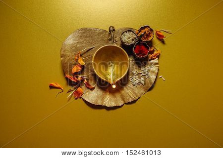 An artistic and rustic background for the Indian Diwali festival. A burning traditional diya placed on a golden leaf with haldi-kumkum. Deepavali greeting card cover.