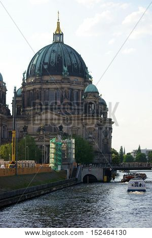 Two passenger ships pass the river Spree at the Berlin Cathedral.
