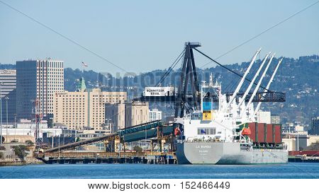 Oakland CA - September 27 2016: Bulk Carrier LA BAMBA loading at Schnitzer Steel Port of Oakland. Schnitzer Steel recycles scrap metal into finished steel products such as rebar and wire rod.