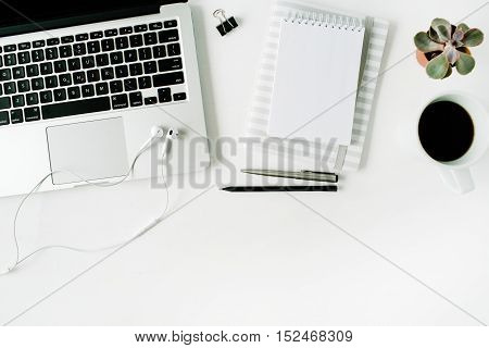 Flat lay home office workspace with laptop diary coffee succulent on white background.
