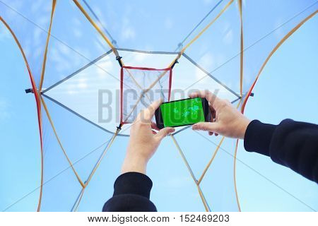 Man in bivouac with transparent gauze dome and blue cloudy sky above looking at map on smartphone holded in hands poster