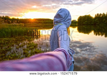 Girl in a white hoodie holding a guy's hand on the beach at the sunset