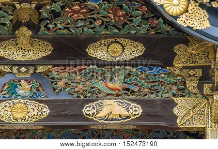 Kyoto Japan - September 19 2016: Closeup of wood carving at Kara-mon gate in Nijo Castle. Shows a colorful bird a man struggling with a dragon and golden decorations.
