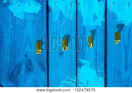 Number 2017 with shadow on the grunge blue wooden background. New Year concept