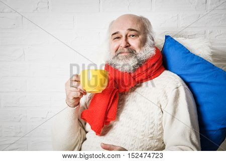 Portrait of Happy Senior Man with Beard in Winter Clothes Drinking Tea. Mature Old Man with Mug Relaxing. White Brick Wall Background. Copy Space.