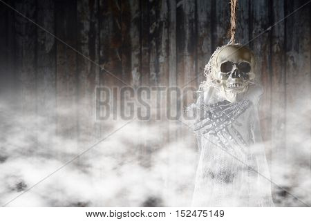 Terrible skeleton on the gallows on a background of smoke.