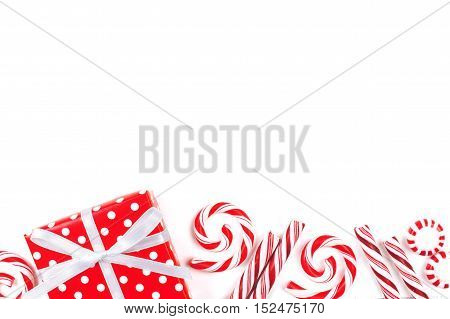 Christmas Border Of Red And White Gifts And Peppermint Candies Over A White Background