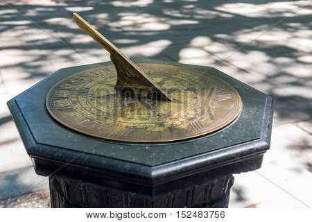 Old brass sundial on a stone or marble column on the corner of a sidwalk poster