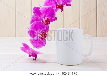 White coffee mug mockup with purple orchid. White coffee cup mock-up for brand promotion. Empty mug mockup for design presentation.