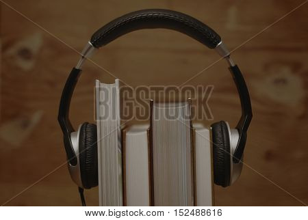 the concept of using audio books put on the headphones on the book on the background of wooden wall