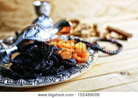 Dried oriental fruit on a silver tray on a wooden table light