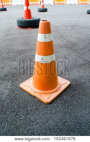 traffic cone, with white and orange stripes on gray asphalt