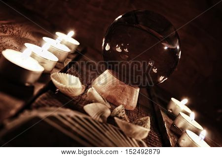 crystal ball for predicting the fate and supernatural action on the table from the old mahogany with candles and cards