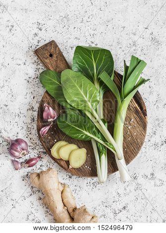 Fresh ingredients - chard leeks ginger garlic. On a light background top view