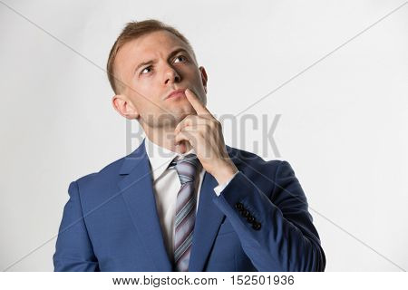 Businessman with finger on face thinking