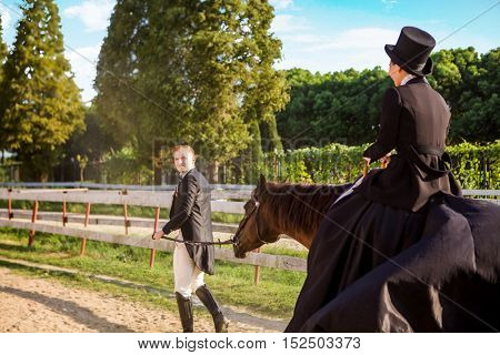 Well-dressed man pulling woman sitting on horse at field