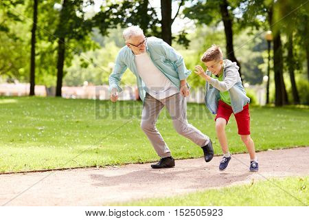 family, generation and people concept - happy grandfather and grandson racing at summer park