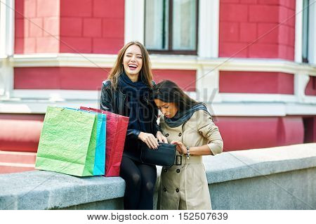 happy girls ,watch something in the bag after a shopping trip .Surprise of the amount spent