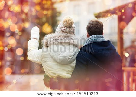 holidays, winter, christmas, tourism and people concept - close up of couple in old town from back over lights