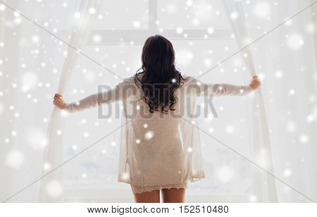 people, winter, christmas and morning concept - close up of happy woman opening window curtains at home over snow