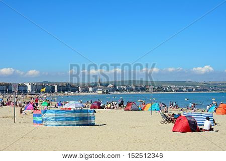 WEYMOUTH, UNITED KINGDOM - JULY 18, 2016 - View along the beach towards the promenade buildings with holidaymakers enjoying the sunshine Weymouth Dorset England UK Western Europe, July 18, 2016.