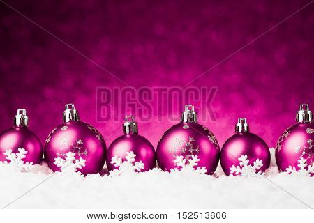 purple christmas balls on snow. studio shot